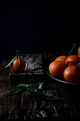 Clementines with leaves on wood. Moody photography
