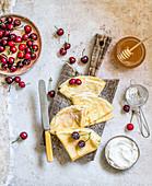 Crepes serviert mit Kirschen, Sahne, und Honig