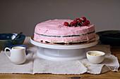 Vegan tart with raspberries and chocolate on white cake stand