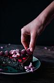 Ein Stück Mohnkuchen dekoriert mit gefrosteten Himbeeren und rosa Blüten