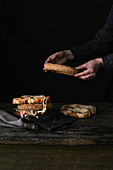 A Women s Hands Taking Bagel on a Black Background
