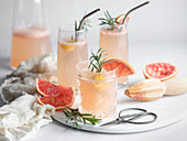 Three glasses of grapefruit cocktail on a marble tray with rosemary and grapefruit slices, pitcher and mousseline napkin