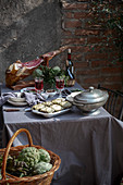 Mediterranian Table cloth with whole ham jamon serrano leg, baked artichokes and red wine