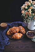 Croissants, Marmelade und eine Tasse Kaffee auf rustikalem Holztisch
