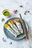 Vegane Frühlingsrollen mit Essblüten in Reispapier und grüner Chili-Dip