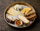 Cheese Plate with different types of cheese Snack assortment on dark background