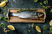 Raw fresh uncooked fish sea bass on ceramit plate ready to cook with lemon, sea salt, rosemary, green salad