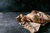 Whole raw organic uncooked farmer chicken poultry on crumpled craft paper over black concrete background