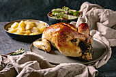 Whole baked chicken poultry on ceramic plate served with potatoes and young beetroot salad leaves