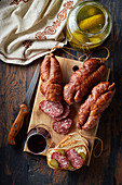 Several hard sausages with pickles and red wine