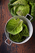 Whole cabbage, and savoy cabbage leaves in a vintage colander