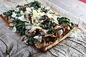 Spinach mushroom flatbread pizza with shaved parmesan cheese