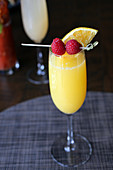Mimosa cocktail with raspberry garnish