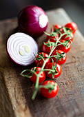 Bunch of fresh ripe tomatoes cherry and cut red onion bulbs placed on wooden cutting board