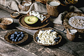 Healthy breakfast. Variety of breakfast dishes sprouted wheat, yogurt, kefir, cottage cheese, avocado, rye bread, seeds, nuts and berries assortment in ceramic bowls over rustic wooden table.