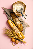 Top view of white and wholegrain baguettes and baking ingredients over pink background