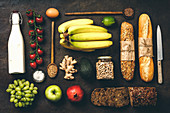 Flat lay of healthy food - milk, bread, fruits, vegetables, grains and legumes on rustic background