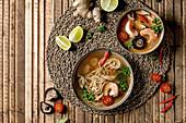 Thailändische Tom Yum Kung und asiatische Nudelsuppe auf Tischset