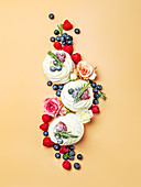 Beautiful creative layout of mini pavlova cakes in top view. Mini pavlova with flowers and berries on cream yellow background. Vertical