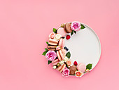 Beautiful composition with french macarons, flowers and berries on craft plate over pink background