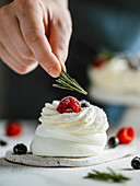 Female fingers holds rosemary to decorate mini Pavlova cake with fresh berries