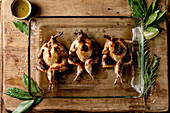 Roasted grilled butterfly quails in glass baking tray with greens, salt and olive oil