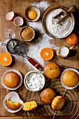 Mandarinen-Muffins mit Backzutaten auf rustikalem Holzbrett