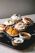 Homemade citrus oranges or clementines sweet muffins cupcakes in baking tray with different cream, pistachio, caramel toppings in bowls