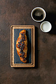 Traditional french puff pastry and chocolate, croissant on slate wooden board with paper cups of coffee and milk