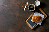 Traditional french puff pastry chocolate bun on slate wooden board with paper cup of coffee and milk