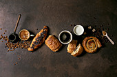 Variety of traditional french puff pastry raisin and chocolate buns, croissan, cups of coffee and milk