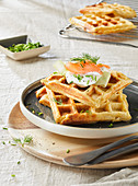 Potato waffles with salmon, sour cream, cucumber, dill and chives
