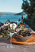 Table with seafood - fish and mussels, white wine with sea on background