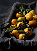 Fresh Tangerines with Leaves on grey linen napkin