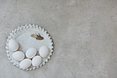 Ceramic plate with white eggs and a feather