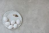 Keramikteller mit weissen Eiern und Feder