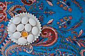 White eggs on a blue tablecloth with a floral pattern