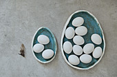 Egg-shaped ceramic plates with white eggs
