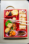 Japanese bento box with rice, omelette, prawn and tofu