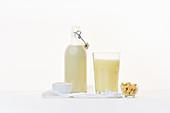 Reismilch und Cashewmilch in Bügelflasche und Glas