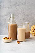 Schokoladen-Mandelmilch in Flasche und Gläsern
