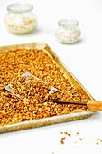 Selbstgemachtes Granola-Müsli aus Haferflocken und Quinoa auf Backblech