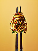 Chinese noodles on chop sticks, against a yellow background