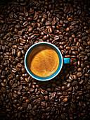 Eine Tasse Espresso inmitten von gerösteten Kaffeebohnen