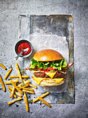 A beef burger with bacon, fries and tomato sauce against a light background
