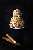 Gourmet coffee ice cream with rolled wafer biscuits.