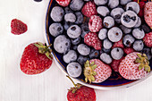 Plate with fresh and frozen various berries (bilberry, raspberry, blueberry, strawberry)