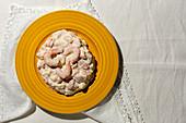 Traditional Russian homemade salad with potatoes, mayonnaise sauce, prawns, carrots, tuna