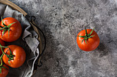 Wet clean tomatoes placed on gray fabric napkin on grey concrete table background