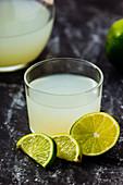 Homemade refreshing lemonade in server in glasses on black marble background